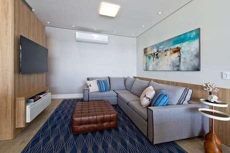 45. Sala de estar com tapete, almofadas e quadro em tons de azul. Projeto de Espaço do Traço