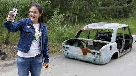 Turista tira uma selfie sorridente na zona de exclusão de Chernobyl, na cidade abandonada de Pripyat