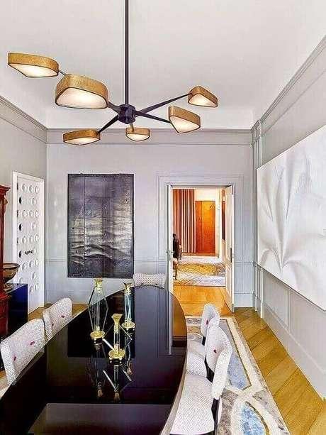 61. A sala de jantar tem lustre com detalhes em dourado e design arrojado. Fonte: Pinterest