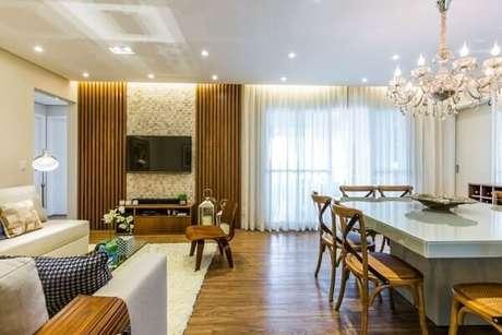 47. Em salas integradas, o mais usual é usar o lustre sobre a mesa de jantar. Projeto de By Arquitetura