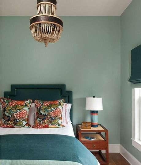 29. Quarto decorado com tons de verde e com lustre para quarto