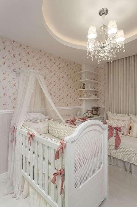35. Quarto de bebê menina decorado com papel de parede florido e lustre clássico