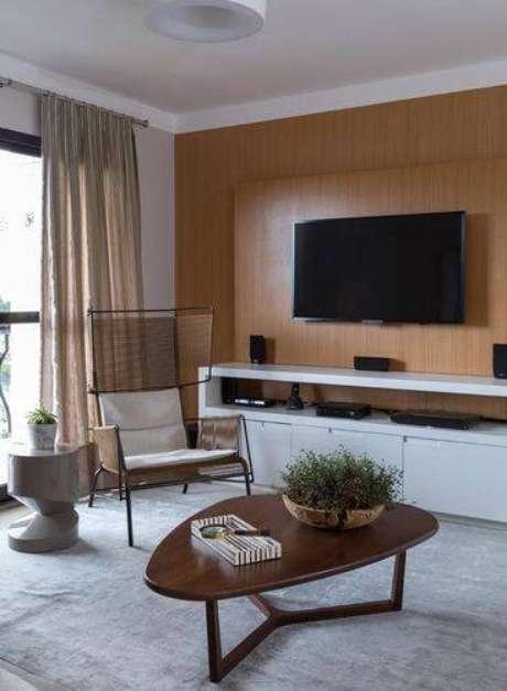 7. Você pode usar o mesmo material do painel para TV para revestir a parede, fica bem moderno. Projeto de Ana Yoshida