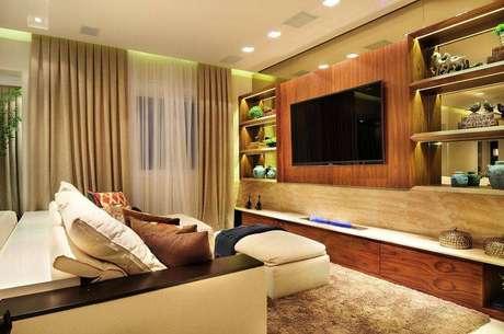 13. Um painel para TV com visual de madeira rústica tem todo um charme especial, como esse que combina com o rack. Projeto de Quitete Faria