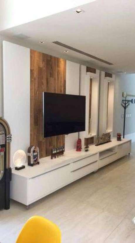 23. Mesclar texturas diferentes no painel para TV deixa o ambiente mais dinâmico, como nesse projeto de Roselle Ayres com madeira rústica e um material liso branco