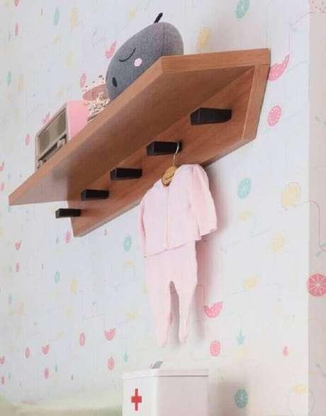 3. A prateleira de madeira com ganchos é muito utilizada para decoração de quarto de bebê – Foto: Guilherme Barbosa