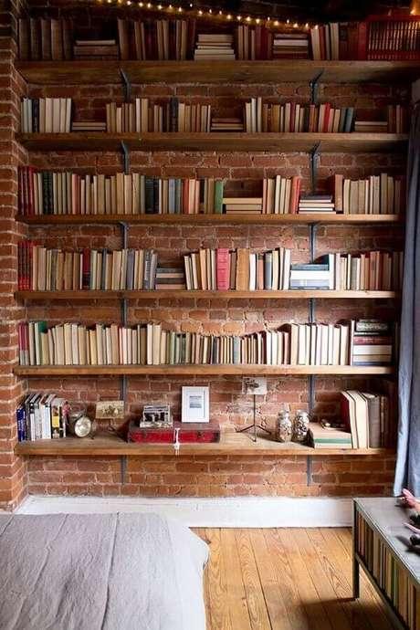 8. Decoração rústica com prateleira de madeira para livros instalada em parede de tijolinhos – Foto: Apartment Therapy