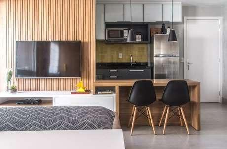 55. Painel para TV feita de madeira ao lado do balcão da cozinha. Projeto de Danyela Correa