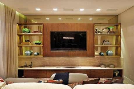 48. Painel para TV feito de madeira e posicionado em sala clara. Projeto de Quitete Faria