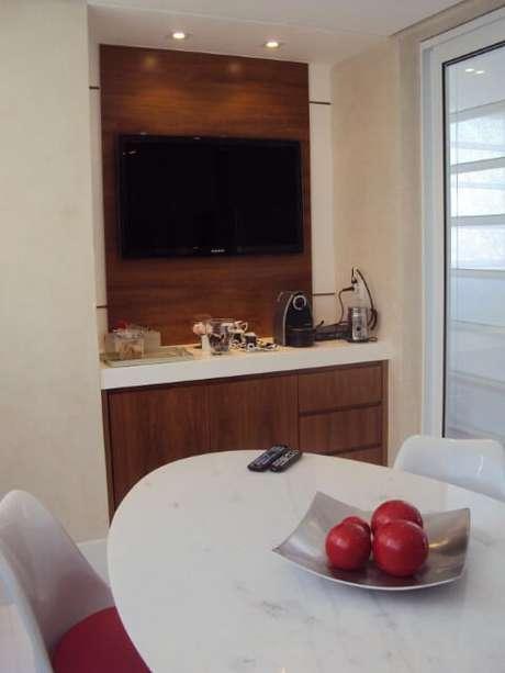 56. Painel para TVfeito de madeira e posicionado na sala de jantar. Projeto de Denise Barbuy Paes de Almeida