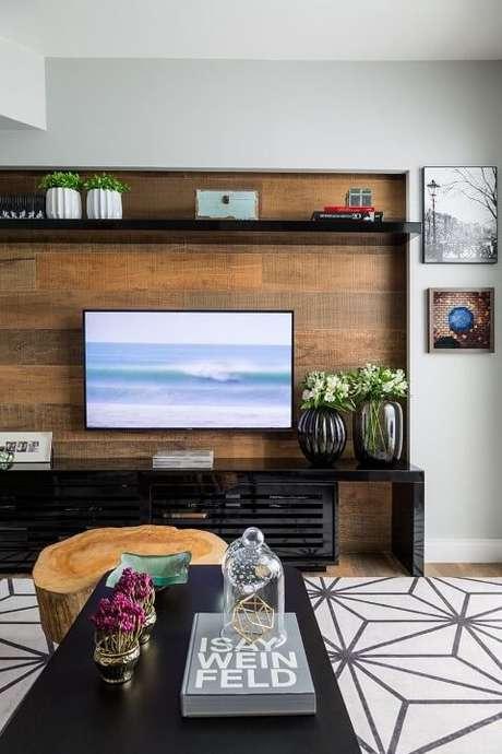 47. Painel para TV de madeira com rack e prateleira pretos. Projeto de Studio Novak
