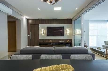 59. Painel para TV com iluminação aos lados em salas integradas. Projeto de Arquiteta Petini