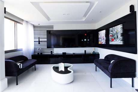 43. O painel para TV que abrange dois lados da sala dá a sensação de profundidade no ambiente. Projeto por Elaine Fonseca