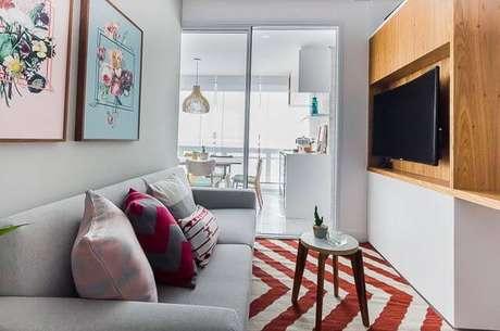 33. Sala de estar pequena com painel para TV de madeira. Projeto por Duda Senna