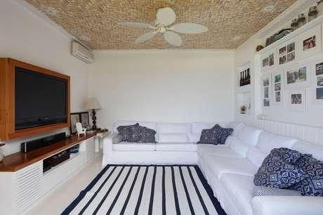 39. Sala de estar em L com estofados brancos e painel para TV em madeira. Projeto por Paola Ribeiro