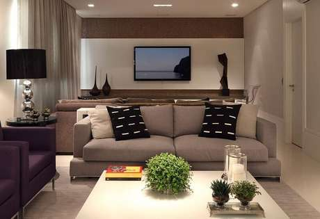 41. Painel para TV branco em parede marrom, deixando o ambiente mais sóbrio e elegante. Projeto por Rocha Andrade