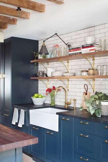 39. Decoração com prateleira de madeira para cozinha azul com detalhes em dourado – Foto: HGTV