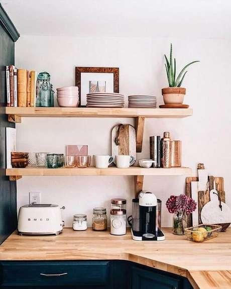 40. Prateleira de madeira para cozinha com armário azul marinho – Foto: Pinterest