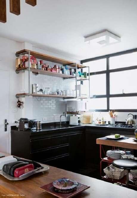 43. Prateleira de madeira para cozinha com subway tile e armário planejado preto – Foto: Histórias de Casa