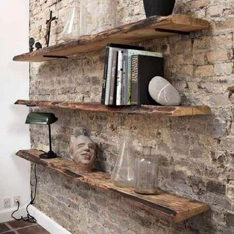 60. Prateleira de madeira rústica para decoração de parede de tijolinho – Foto: Pinosy