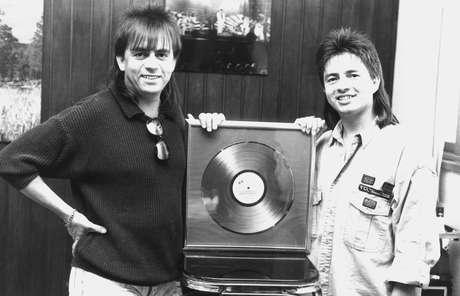 """A dupla sertaneja Chitãozinho e Xororó posa ao lado do disco de diamante conquistado pela venda de 1,5 milhão do disco """"Meu Disfarce"""", de 1987, no escritório da dupla, em São Paulo"""