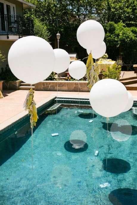 36. Decoração de festa na piscina com balões brancos flutuando sobre a piscina – Foto: Wedding Ideas