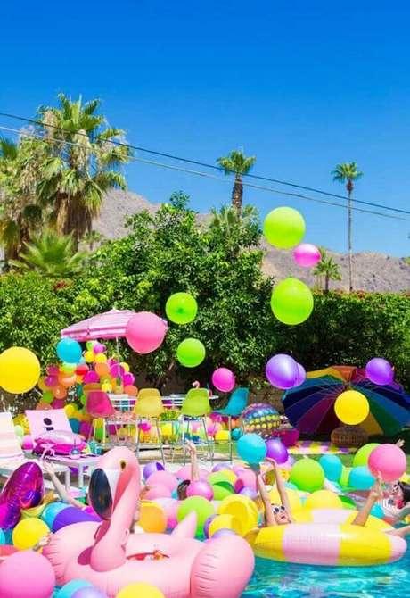 38. Linda decoração de festa na piscina com muitas boias e balões coloridos – Foto: Pinterest