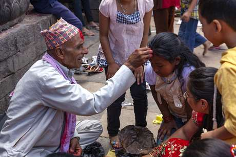Profeta Nepal e mulheres vestidas roupas tradicionais vermelha no evento religioso no templo