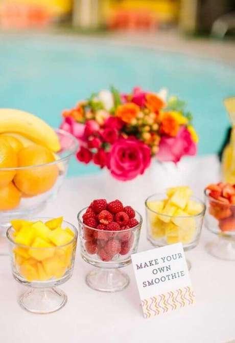 64. Mesa de doces e comidas para festa na piscina decorada com flores – Foto: Bacuri Festas