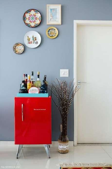 17. Mini geladeira vermelha serve de base para as bebidas. Fonte: Histórias de Casa