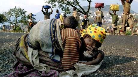 Mulher desaba aos prantos, com o bebê nas costas, após fugir de Ruanda em 1994