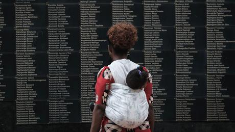 Mulher observa mural com o nome das vítimas do genocídio, que completa 25 anos