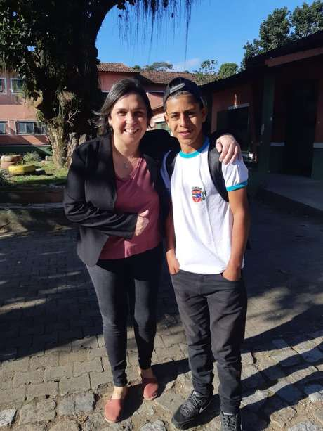Luan com a nova professora no dia que voltou para a escola, após perder os dois primeiros meses deste ano