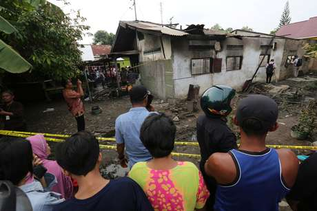 Locals look at a house used as a factory producing matchsticks after a fire swept through, at Binjai district in Langkat, North Sumatra province, Indonesia, June 21, 2019 in this photo taken by Antara Foto. Antara Foto/Adiva Niki/ via REUTERS ATTENTION EDITORS - THIS IMAGE WAS PROVIDED BY A THIRD PARTY. MANDATORY CREDIT. INDONESIA OUT.