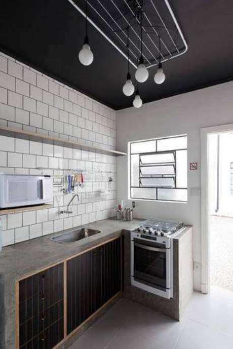 8. Cozinha compacta estilo escandinavo com bancada de cimentício e teto e armários escuros. Projeto de Felipe Hess