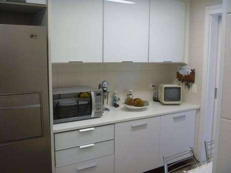 21. Cozinha compacta planejada com armários brancos. Projeto de Ana Laura Wolcov