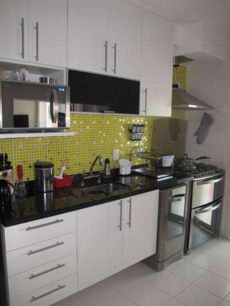 13. Cozinha pequena com pastilhas amarelas, armários brancos e bancada de granito preto absoluto. Projeto de Mariane Battaglia