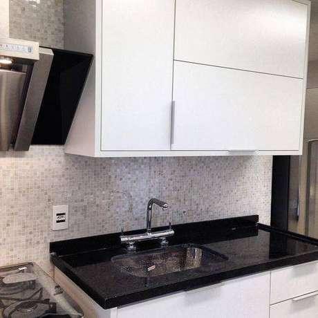 26. O granito preto absoluto contrasta de maneira elegante com armários brancos. Projeto de Iago Patucci