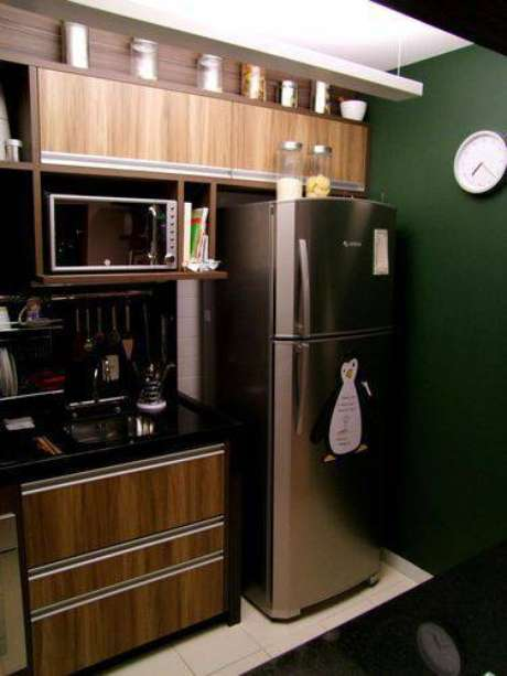 33. Cozinha compacta com armários de madeira, bancada de granito e parede verde escuro. Projeto de Cristina Marcovecchio