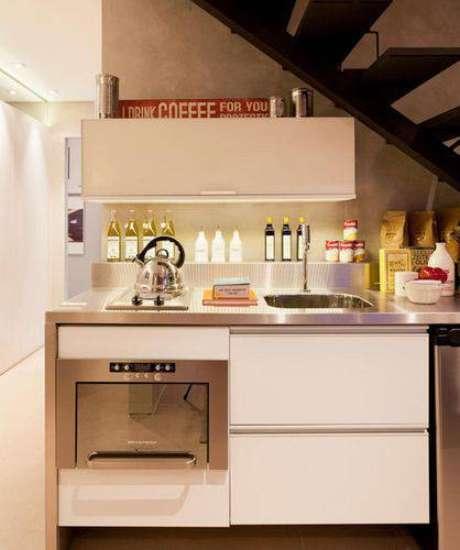 27. Esta cozinha compacta embaixo da escada otimiza o pouco espaço com móveis planejados. Projeto de Basiches Arquitetos