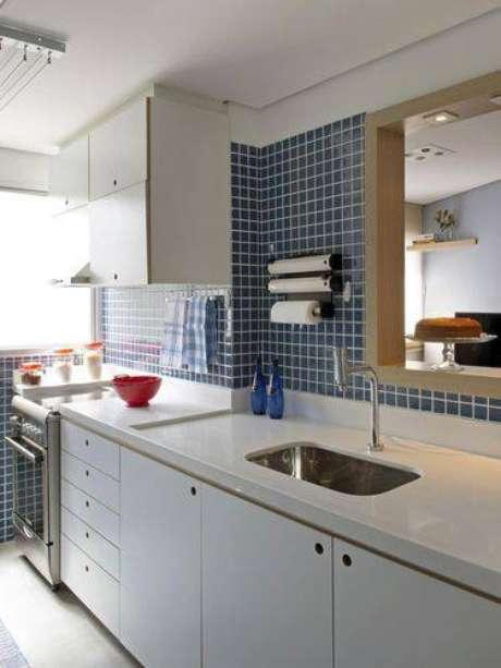 34. Cozinha americana pequena com revestimento de pastilhas azuis e bancada branca. Projeto de Marina Carvalho