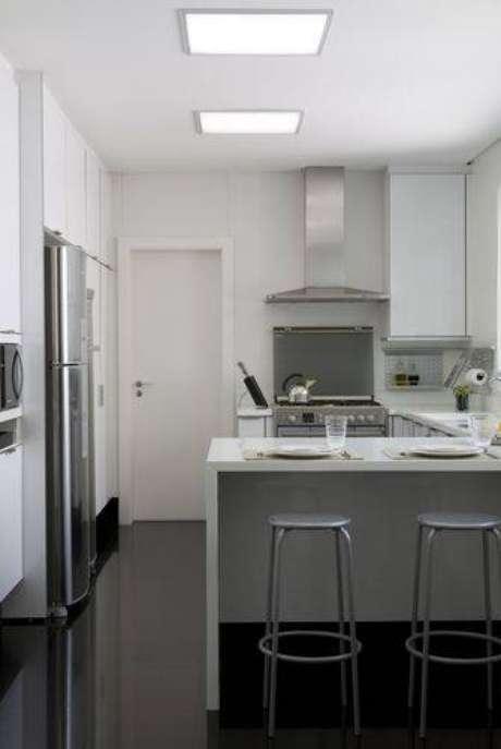 """4. Cozinha compacta com geladeira, fogão e pia formando o """"triângulo de trabalho"""". Projeto de Marcelo Rosset"""
