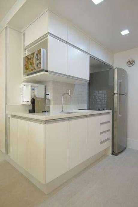 12. Cozinha compacta com armários planejados brancos e parte do revestimento de azulejo metro white. Projeto de Ravaglia Philot