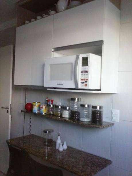 35. Cozinha compacta com armário aéreo branco e bancada de granito. Projeto de Madik Correia Dutra
