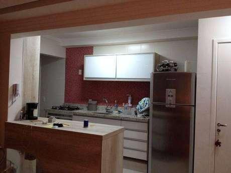 15. Cozinha compacta americana pequena com pastilhas vermelhas na área da pia. Projeto de Natalia Ribas
