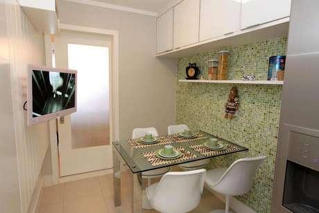 41. Cozinha compacta e moderna com mesa de vidro e armários brancos. Projeto de Lorrayne Zucolotto