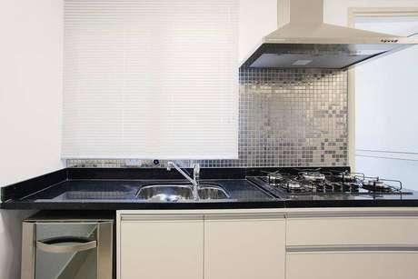 17. Cozinha compacta com balcão de granito preto e pastilhas prateadas. Projeto de Sesso Dalanezi