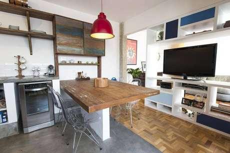 43. Televisão e prateleira na cozinha compacta americana servem para os dois ambientes. Projeto de Carla Cuono