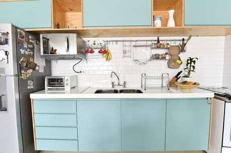 38. Cozinha compacta com armários azuis e revestimento de azulejo metro white. Projeto de Carla Cuono