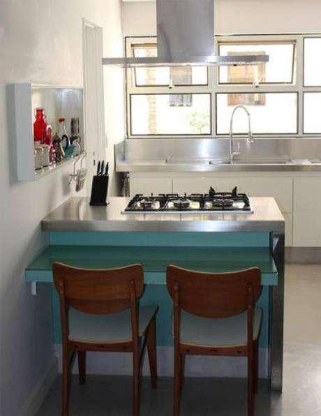 14. Cozinha compacta com bancada com cooktop e mesa pequena. Projeto de Celine Desroches